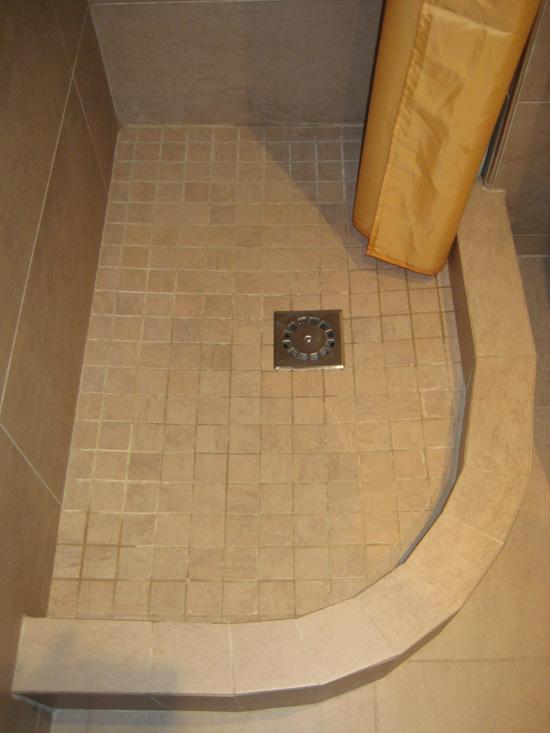 Plato de ducha de obra a medida con forma semicircular, revestido con baldosa antideslizante