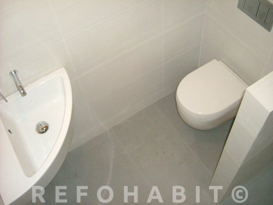 Hacer baño adicional en piso de Horta, Barcelona. Lavamanos esquinero pequeño e inodoro suspendido para ahorrar espacio.