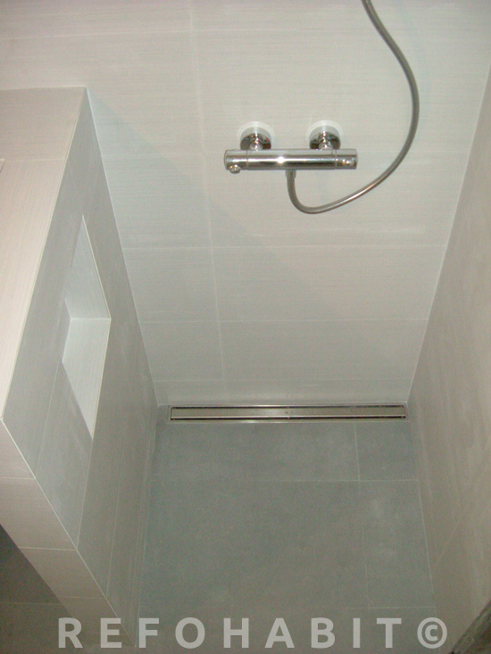 Plato de ducha a nivel, con desagüe sumidero en canal de acero inox y estantería de obra para botes.