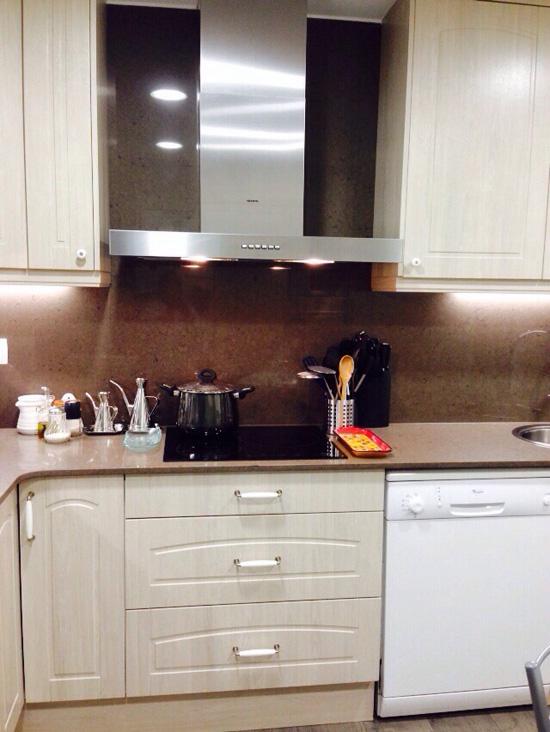 Reforma de cocina, zona de cocción con aplacado hasta el techo y armarios altos.