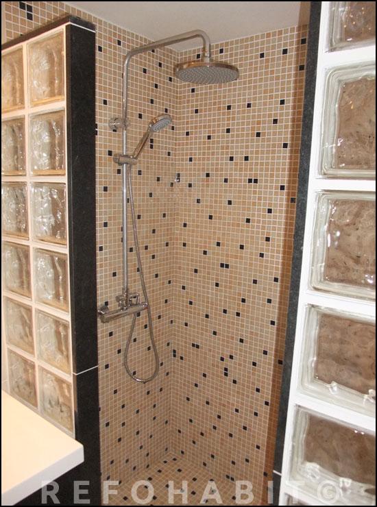 DESPUÉS del cambio de bañera por ducha, paredes y base revestidos con malla de gresite (mosaico de vidrio) y con mampara de cubos de pavés con acabados en Silestone negro.
