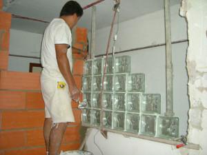 Aquí estoy yo... colocando las piezas de pavés en la pared entre cocina y pasillo.